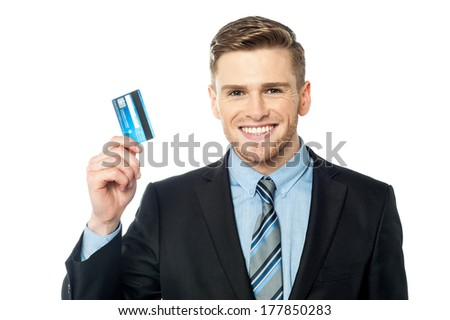 Smiling corporate executive showing his credit card - stock photo