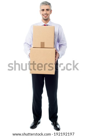 Smiling corporate man holding stack of boxes - stock photo