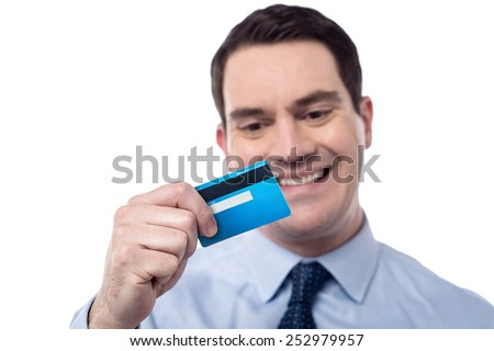 Smiling corporate man looking his new debit card - stock photo