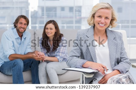 Smiling couple and therapist looking at the camera - stock photo