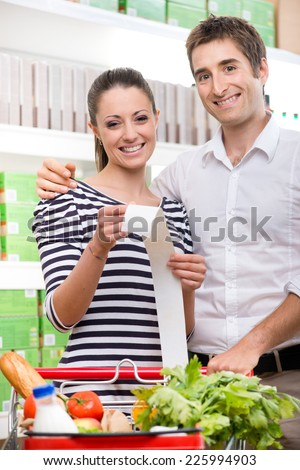 Smiling couple at store holding a long grocery receipt with shopping cart on foreground. - stock photo