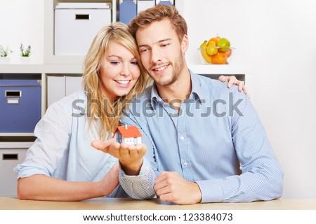 Smiling couple carrying a little home on the hands - stock photo