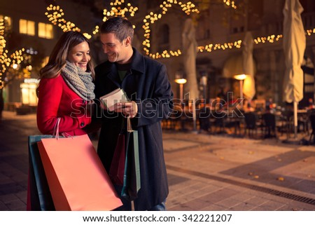 Smiling couple checking shopping list for Christmas on decorated car-free street - stock photo