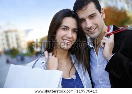 Smiling couple doing Christmas shopping - stock photo