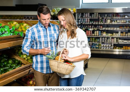 Smiling couple doing shopping in grocery store - stock photo