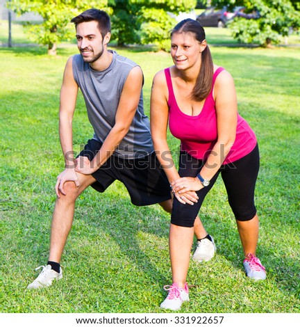 smiling couple doing streching in the park - stock photo