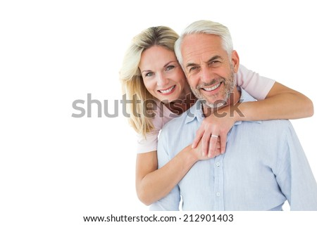 Smiling couple embracing and looking at camera on white background - stock photo