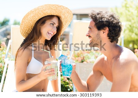 Smiling couple enjoying a cocktail while sitting on beach chairs - stock photo
