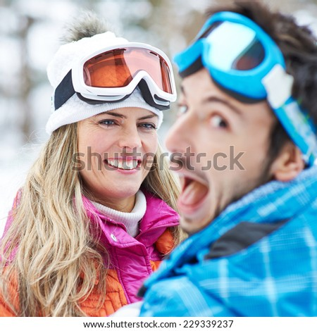 Smiling couple having fun in a ski trip holiday in the snow - stock photo