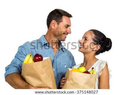 Smiling couple holding grocery bags on white screen - stock photo