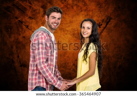 Smiling couple holding their hands and looking at camera against shades of brown - stock photo