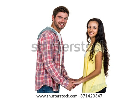 Smiling couple holding their hands and looking at camera on white screen - stock photo