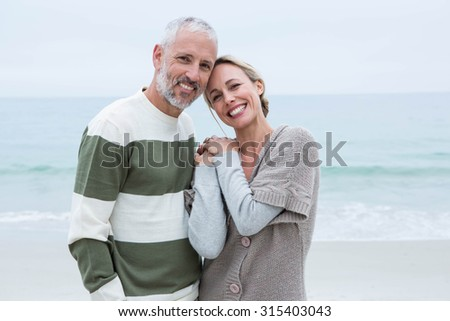 Smiling couple holding their hands at the beach - stock photo