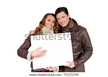 Smiling couple holding white message board - stock photo