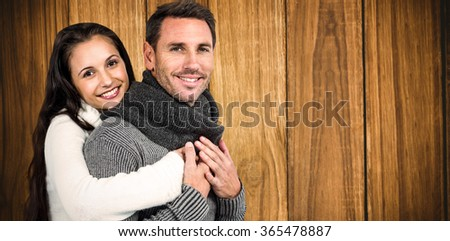 Smiling couple hugging and looking at camera against wooden background - stock photo