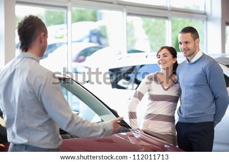 Smiling couple in a car shop with a car dealer - stock photo