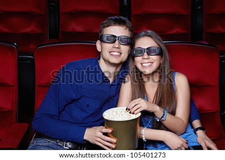 Smiling couple in the cinema - stock photo