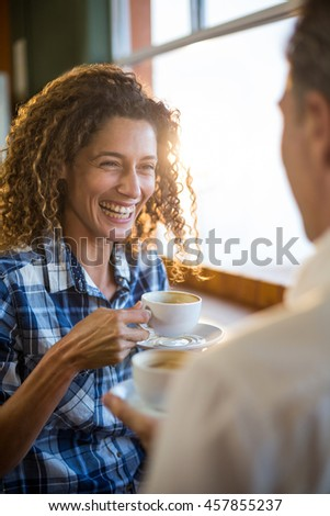Smiling couple interacting with each other in super market while having tea - stock photo