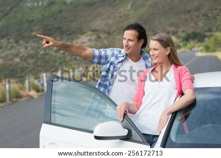 smiling couple looking away outside their car - stock photo