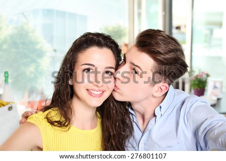 smiling couple make a self ie in coffee bar - stock photo