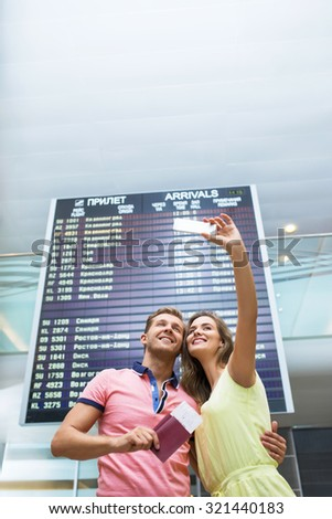 Smiling couple making selfie at the airport - stock photo
