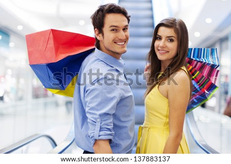 Smiling couple on escalator in shopping mall - stock photo
