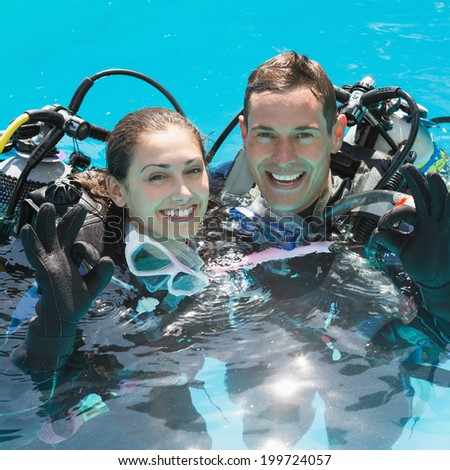 Smiling couple on scuba training in swimming pool showing ok gesture on a sunny day - stock photo