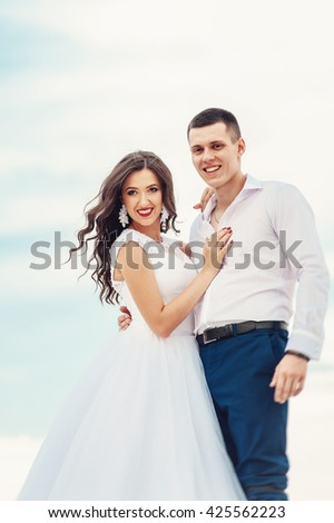 Smiling couple on the wedding ceremony. Beautiful brunette woman with long wavy hair hugging handsome man. Happy new family concept. Stylish newlyweds on their wedding day walking outdoors. - stock photo