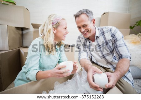 Smiling couple packing mug in a box at home - stock photo