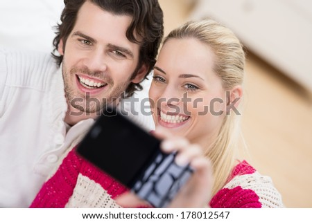 Smiling couple pose with their heads close together for a self portrait on their smartphone - stock photo