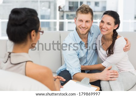 Smiling couple reconciling at therapy session in therapists office - stock photo