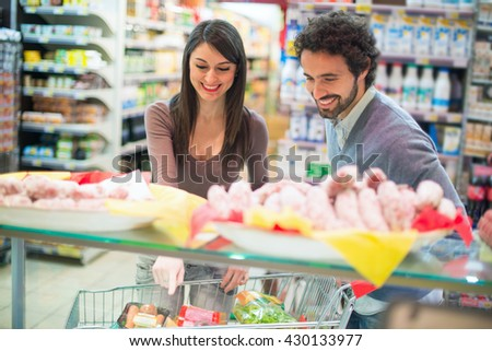 Smiling couple shopping at the grocery store - stock photo