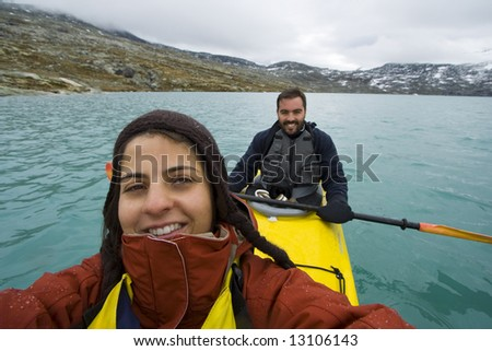 smiling couple sitting in kayak on lake Jostedalsbreen - Norway - stock photo