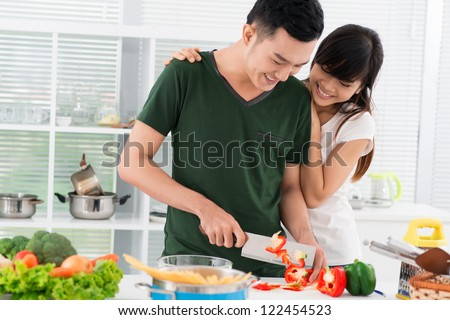 Smiling couple spending time together in the kitchen, guy chopping vegetables - stock photo