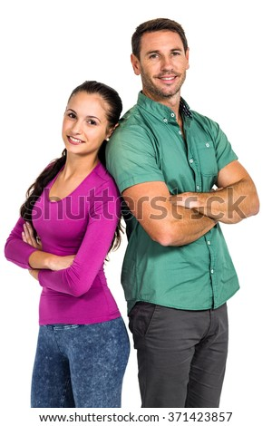 Smiling couple standing back to back with arms crossed looking at the camera on white screen - stock photo