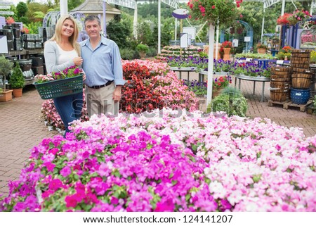 Smiling couple standing in the garden centre while carrying a basket - stock photo