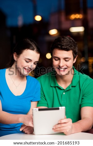 Smiling couple using a digital tablet in restaurant - stock photo