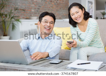 Smiling couple using laptop and smartphone in the living room - stock photo