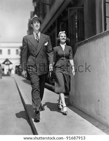 Smiling couple walking on sidewalk - stock photo
