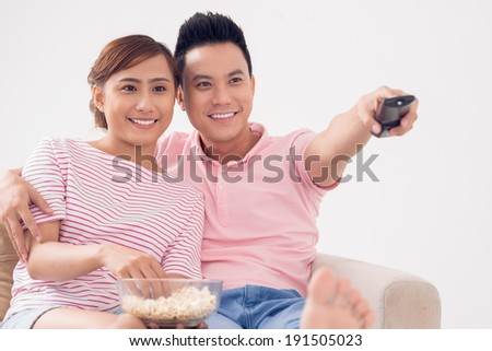 Smiling couple watching tv - stock photo