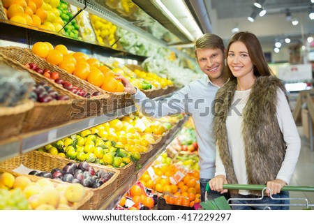 Smiling couple with a cart indoors - stock photo