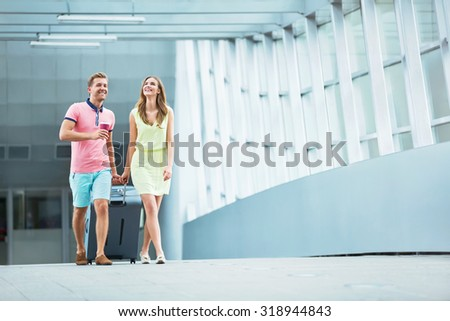 Smiling couple with a suitcase  - stock photo