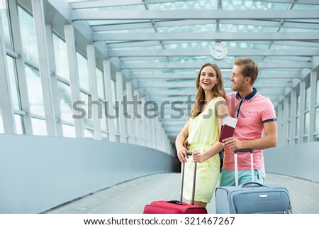 Smiling couple with a suitcase  at the airport - stock photo