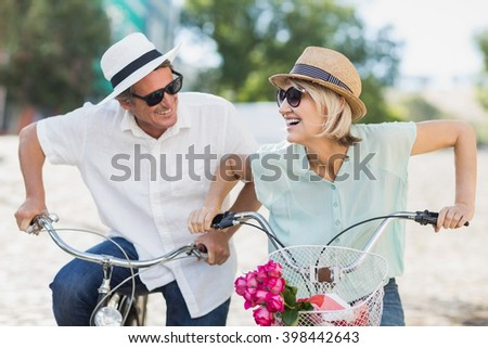 Smiling couple with bicycles in city - stock photo