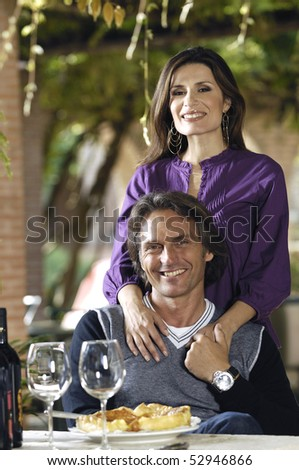 Smiling couple with pies and wine - stock photo
