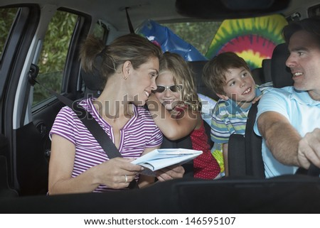 Smiling couple with two happy children in the car - stock photo