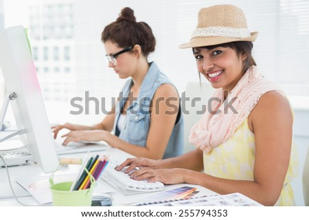 Smiling coworkers typing on keyboard in the office - stock photo