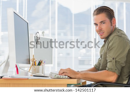 Smiling creative business employee working on computer in a modern office - stock photo