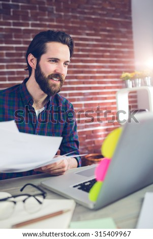 Smiling creative businessman holding documents while using laptop in office - stock photo