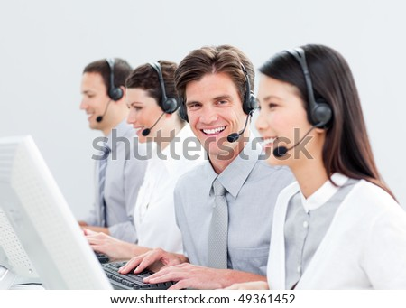 Smiling customer service representatives in a call center - stock photo